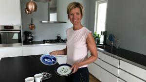 Linda Forth med två assietter i händerna i köket.