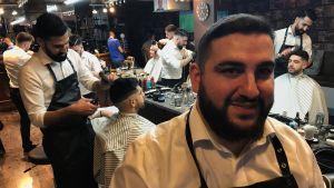 Barberaren Stamatis Zervos, i bakgrunden flera barberare och kunder framför en stor spegel.