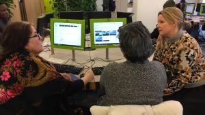 Tre damer diskuterar framför några datorskärmar på ett jobbcenter i Köpenhamn.