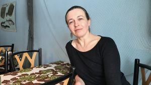Camilla Snickars i svart tröja vid ett bord.
