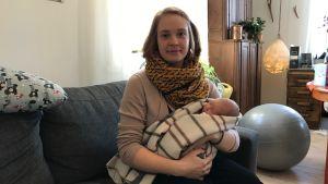Carolina Beijar på soffan med nyfödda dottern Freja.