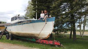 Jessica och Camilla Wiklund sitter på den gamla båten som finns på gården.
