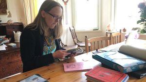Anna Dahlbacka bläddrar i böcker vid bordet.