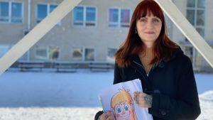 Ung kvinna med bild i handen på skolgård.