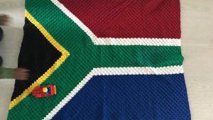 Sydafrikasflagga som virkad filt på golvet.