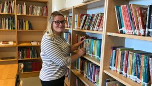 Amra Huric bland böcker i lågstadiets bibliotek.