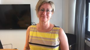 Minister Camilla Gunell står i ett rum med gråa gardiner med en tv i bakgrunden och