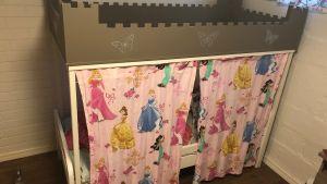 En barnsäng med gardiner framför.