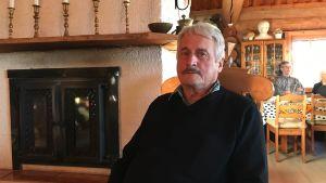 Paavo Juntinen sitter i en gungstol invid en öppen spis.