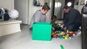 Åsa och Martin bygger lego med Denzel på golvet.