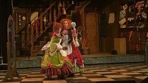 Två damer i färgranna pråliga klänningar på Kungliga Operans scen.