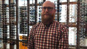 Optiker Kristian Isaksen framför ställning med solglasögon.