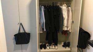 Svarta och gråa kläder hänger i en garderob.