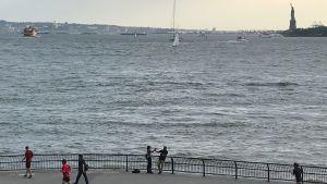 Utsikt över södra Manhattan, joggare på stranden
