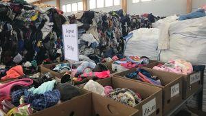 Massor av avlagda kläder i en textilåtervinningsbutik