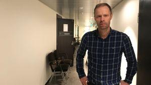 Robert Sundström står i en korridor. Till vänster en rad stolar och en dörr på glänt.