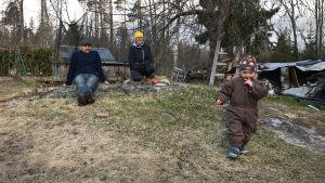 David och Victoria Grönlund sitter på en sten i trädgården och tittar på 2-åriga Ylva.