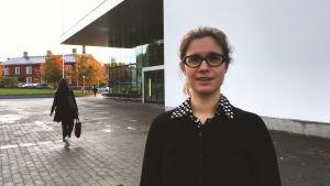 Katarina Hellen står utomhus i höstsolen med universitetsbiblioteket tritonia bakom sig. Hon bär en svart tröja och har svartbågade glasögon.