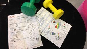 Kaksi kehonkoostumusraporttia ja puntit pöydällä