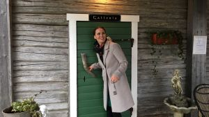 Anne Mattila seisoo galleriansa ovella.