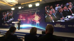 Man stands on a podium talking. In the background the screen Public Broadcasters International Seoul 2018.