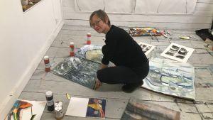Pia Rousku breder ut sina målningar på sittateljégolv