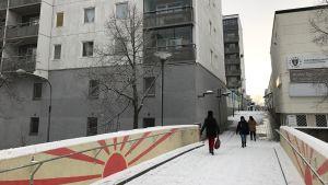 Tre personer promenerar på en gångbro mellan höga bostadshus. Det är snö på marken.