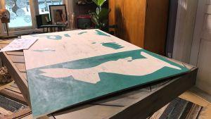 Halvmålad träskiva på ett bord.