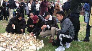 Människor sitter på huk invid en stor samling gravljus, samt tänder egna ljus.