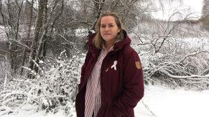 josefin ahslog bär en vinröd vinterjacka i ett snörikt landskap. hon ler.