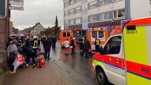 Ambulanser, brandbilar, sjukvårdare och brandmän samlade på en gata.
