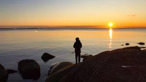 Ett barn står och fiskar i solnedgången på Varlaxudden.