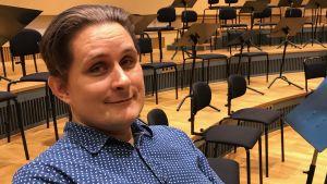 Porträtt på Thorvald Bergström som sitter i korsalen på Kungliga Operan.