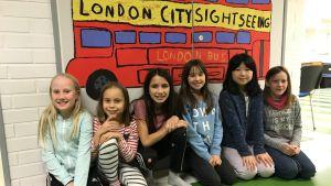 Skolelever framför teckning av skolbuss.