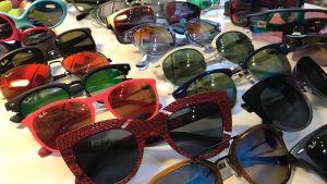 Solglasögon i varierande form och färg utspridda på bord.