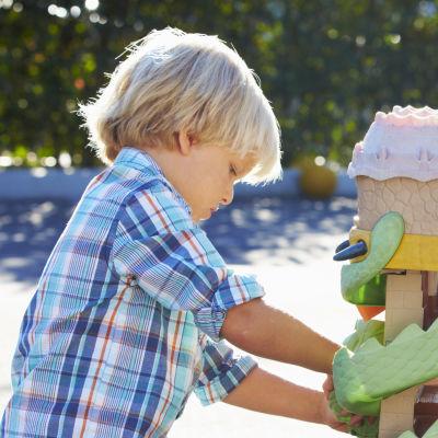 Två pojkar leker med en platsleksak på en skolgård i solen.