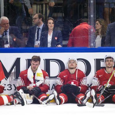 Sveitsin pelaajia pettyneinä MM-finaalin häviämisen jälkeen. Pelaajat istuvat jään pinnassa ja nojaavat kaukalon laitaan.