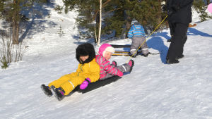 Barn åker pulka som förälder drar