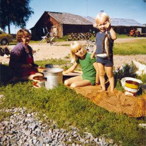 Jouni ja Tanja Järvelä kesäpäivän mummolan pihalla, Jouni näyttää kameralle jonkun onkimia kaloja.