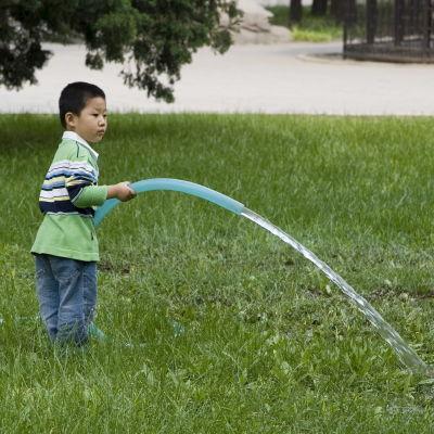 En kinesisk pojke leker med en vattenslang i Peking i Kina den 15 april 2007. Peking, liksom många andra städer i Kina står inför en grundvattenskris.