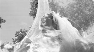 Morsiuspukuinen nainen kesäisessä tuulessa. Kuva elokuvasta Kurjet lentävät.