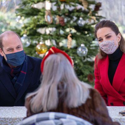 Prinssi William ja herttuatar Catherine keskustelvat iäkkään naisen kanssa. Pöydällä käsidesipullo.