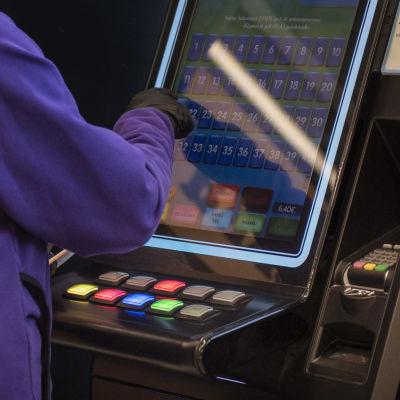 Ihmisen sormi koskettaa peliautomaatin näyttöä, lähikuva.