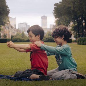 Två små pojkar, Aatos Amine, sitter bakom varandra på en gräsmatta i en park och leker tåg. Stillbild från dokumentären Aatos ja Amine.