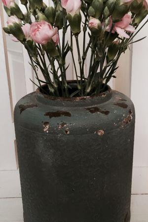 En mörkgrön metallvas med rosa nejlikor.
