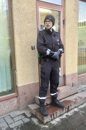 En väktare i svarta kläder står utanför en dörr framför ett gult rappat hus.