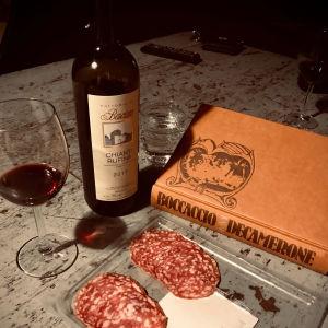 Pöydällä Boccaccion Decamerone-kirja, viiniä ja leikkelemakkaroita.