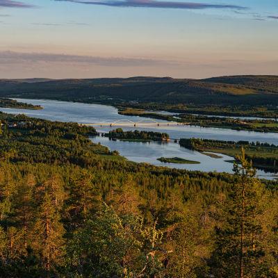 Keskiyön auringossa kylpevä maisema Ylitornion Aavasaksanvaaralta etelään katsottuna, keskellä Tornionjoki.