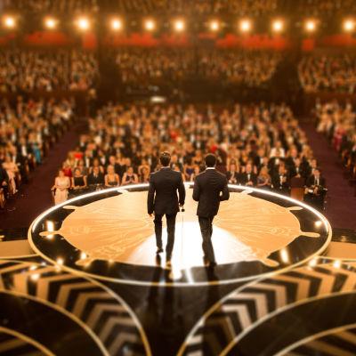 Två män med ryggen mot kameran står på en stor scen och ser ut över en fullsatt sal.