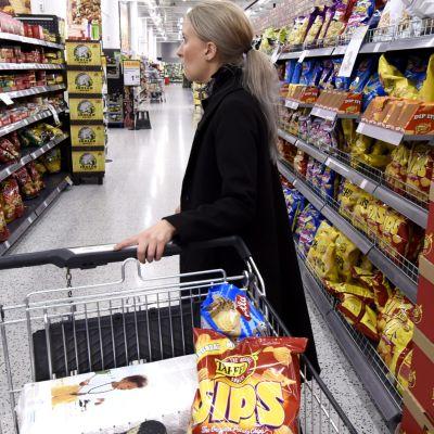 Kvinna med shoppingvagn i supermarket.